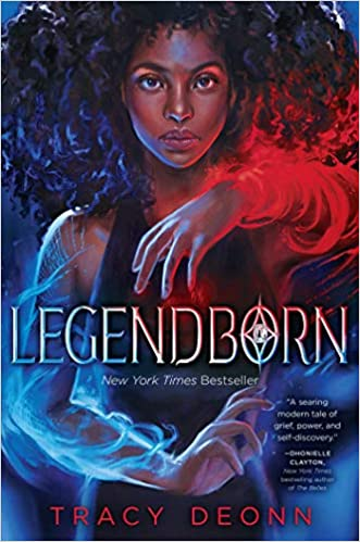 "Alt text: Deep blue book cover with a black girl on the front, waving her arms in front of her while using magic. She is wearing a fitted black dress with tank sleeves. The title ""Legendborn"" is written in various shades of gold across the middle of the book."